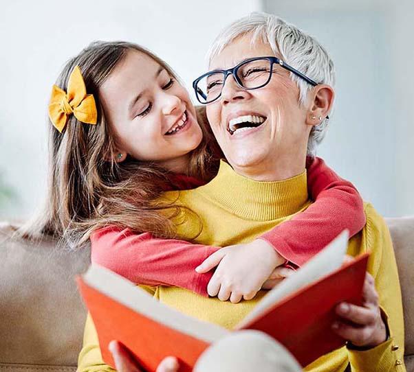 Mujer mayor con gafas ríe con una niña